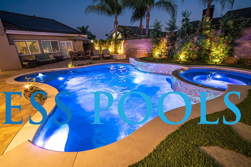 Freeform pool with LEDs at night by Timeless Pools