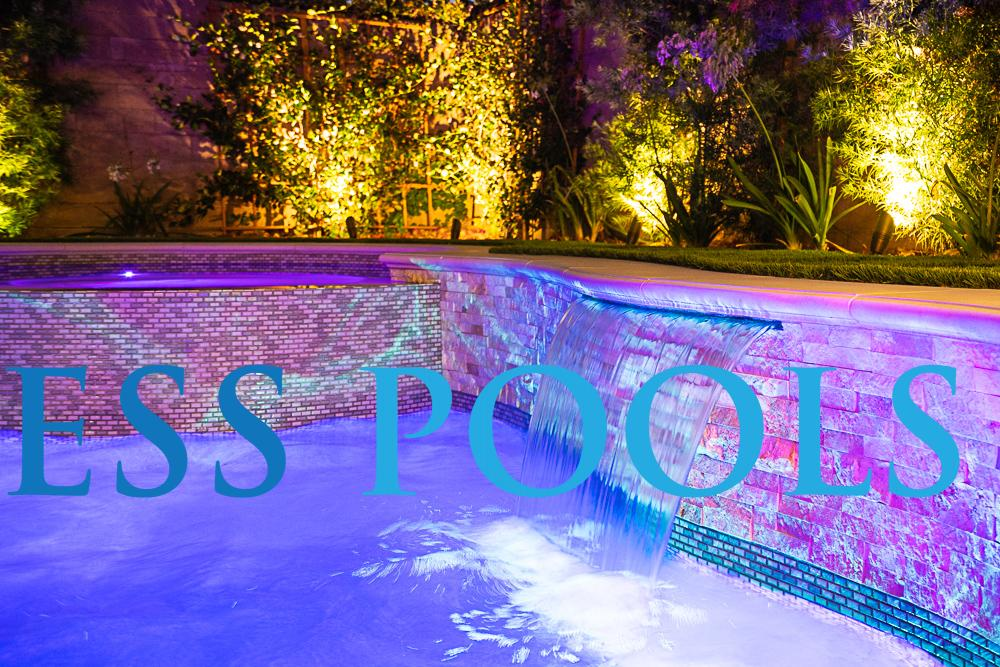 Water descent in a freeform pool at night by Timeless Pools