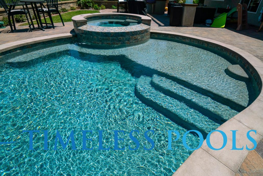 Freeform pool with spa during the day by Timeless Pools